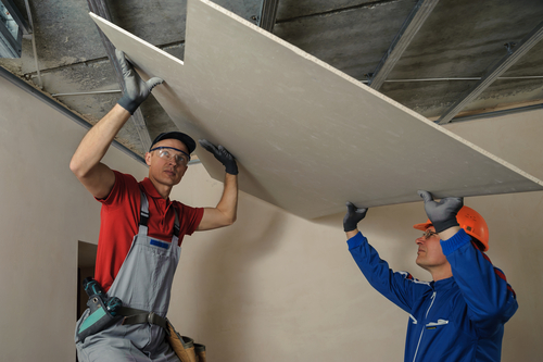 Drywall Contractor employees install sheetrock panels